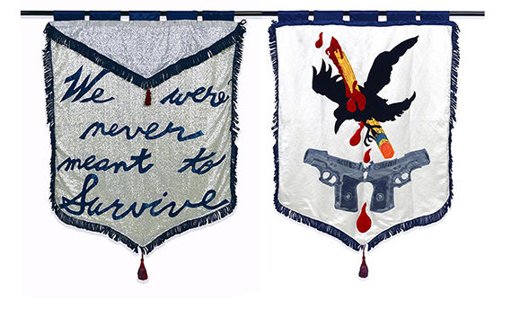 "two banners embroidered by the artist - one with the words ""we were never meant to survive"" the other with an eagle stabbed with a pencil flying over two guns"
