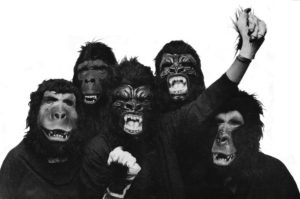 Black and white photo of guerilla girls art group. 5 women dressed in guerrilla masks. One with fist raised in defiance and resistance