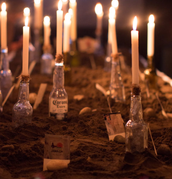 Photo of a table covered in sand and dirt. There are clear glass bottles holding lit white candles.